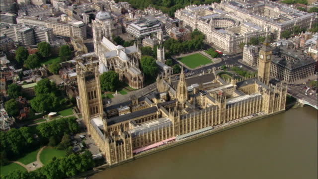 Aerial wide shot pan Houses of Parliament and Westminster Abbey on Thames / London, England