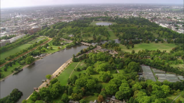 aerial wide shot pan hyde park, serpentine lake and cityscape / london, england - hyde park london stock videos & royalty-free footage