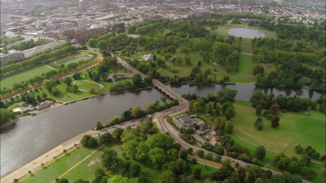 Aerial wide shot pan Hype Park, Serpentine Lake and cityscape / London, England