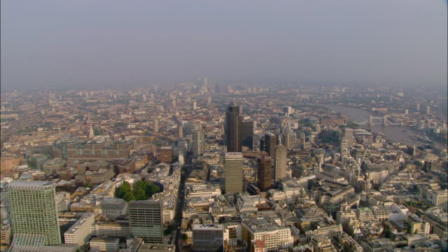 aerial wide shot pan london financial district with thames in background / london - air pollution stock videos & royalty-free footage