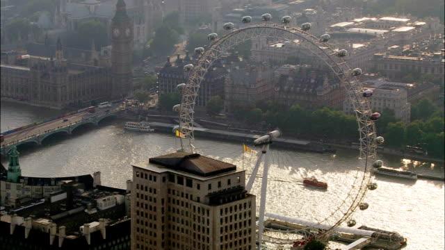 Aerial wide shot pan Millenium Wheel with Houses of Parliament visible across Thames / pan medium shot Millenium Wheel / London, England
