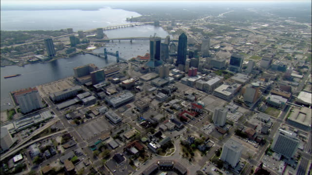 aerial wide shot pan motorways approaching jacksonville/ pan around skyscrapers and waterfront/ boats on st. johns river/ jacksonville, florida - jacksonville florida video stock e b–roll
