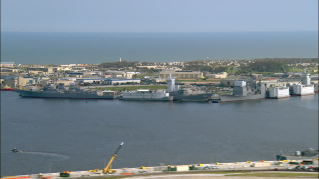Aerial wide shot pan Naval Air Station Jacksonville/ navy boats and moored air craft carrier/ Jacksonville, Florida