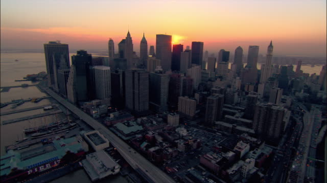Aerial wide shot pan over Brooklyn Bridge down east side of Lower Manhattan/ view of New York Harbor and sun setting over New Jersey/ New York City