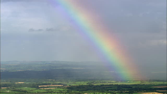 aerial wide shot pan rainbow over green landscape / county cork, ireland - rainbow stock videos & royalty-free footage