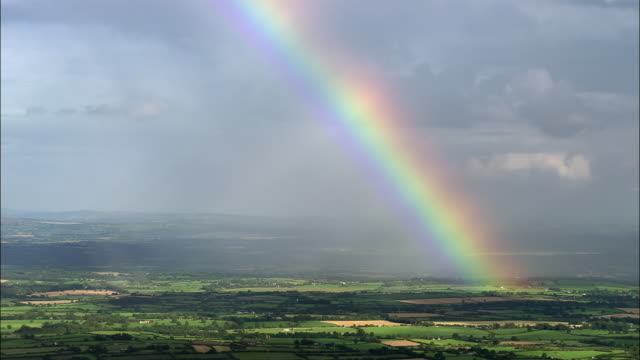 vídeos de stock e filmes b-roll de aerial wide shot pan rainbow over green landscape / county cork, ireland - sorte