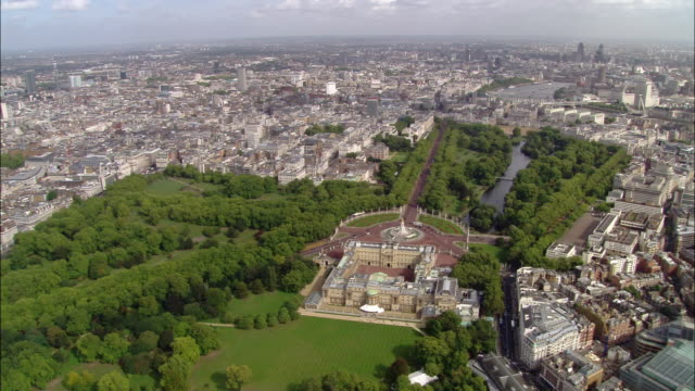 Aerial wide shot pan St. James Park, Buckingham Palace and cityscape / London, England