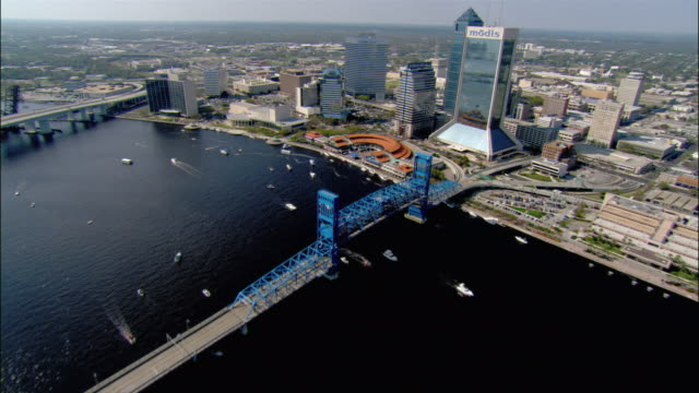 aerial wide shot pan st. johns river, main st. bridge, and waterfront area/ jacksonville landing, modis building, and skyscrapers, past bell south building/ jacksonville, florida - jacksonville florida video stock e b–roll