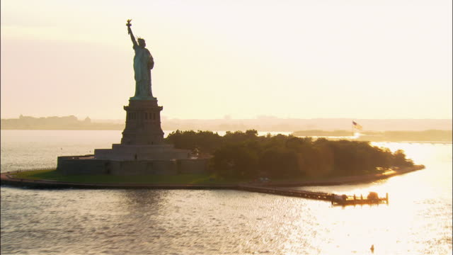 vídeos de stock, filmes e b-roll de aerial wide shot pan statue of liberty at sunset/ zoom out pan statue of liberty, boats in harbour, and lower manhattan cityscape/ new york, new york - cultura americana