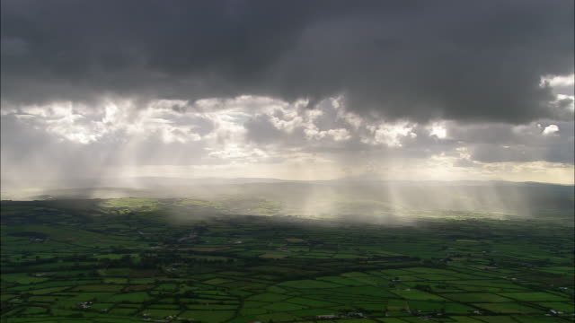 Aerial wide shot pan sunbeams coming through rain clouds over green landscape / County Cork, Ireland