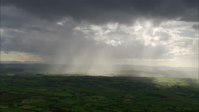 aerial wide shot pan sunbeams coming through rain clouds over green landscape / county cork, ireland - rain stock videos & royalty-free footage
