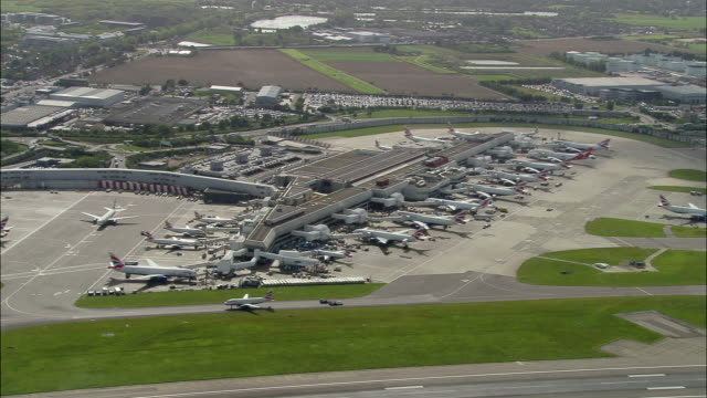 aerial wide shot pan terminal at heathrow airport / london, england - heathrow airport stock videos and b-roll footage