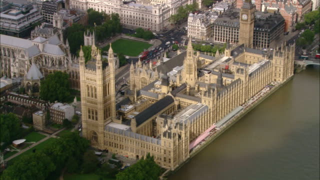 aerial wide shot pan westminster abbey, thames and surrounding area / london, england - parliament building stock videos & royalty-free footage