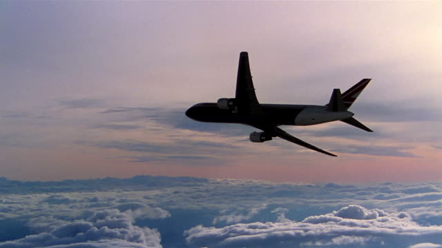 aerial wide shot plane flying away from cam over clouds in sky - commercial aircraft stock videos & royalty-free footage