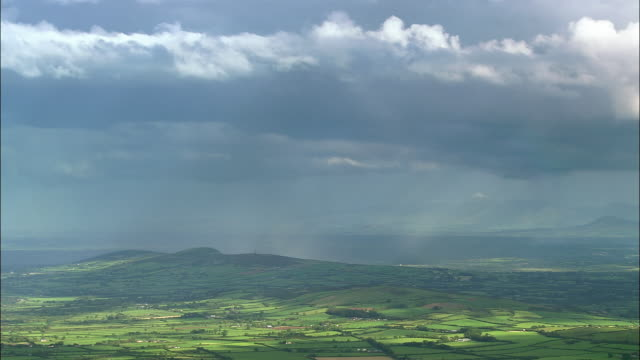 aerial wide shot rain clouds and rainbow over green landscape / county cork, ireland - アイルランド点の映像素材/bロール