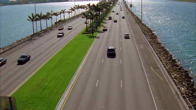 aerial wide shot rear view of suv driving on causeway / long shot traffic on causeway and surrounding water / miami - 1997 stock videos & royalty-free footage