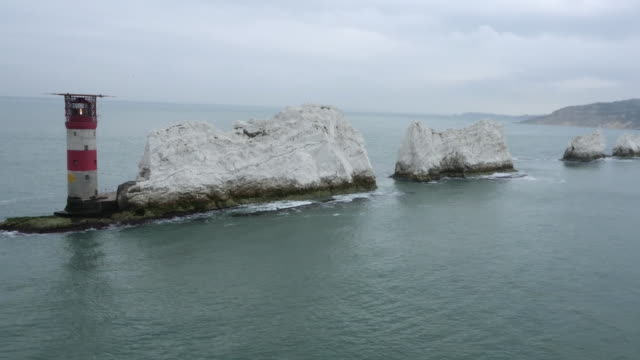 Aerial wide shot showing the Needles Lighthouse and Needles rock formations off the Isle of Wight, UK.