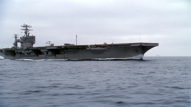 aerial wide shot side view of uss carl vinson sailing in pacific ocean / circling around bow to other side - us navy stock videos & royalty-free footage