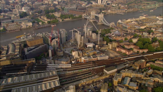aerial wide shot trains moving into london bridge station with tower bridge in background / london, england - london bridge inghilterra video stock e b–roll