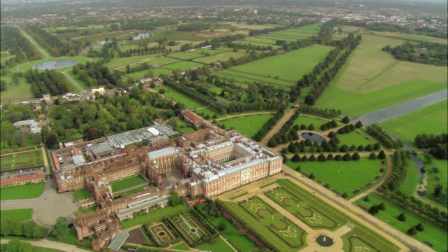 aerial wide shot view over hampton court palace to east garden / pan view of palace front with thames in background / surrey, england - richmond upon thames stock-videos und b-roll-filmmaterial