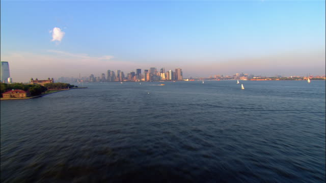 aerial wide shot zoom in across new york harbour, past liberty and ellis islands to lower manhattan/ new york, new york - hafen stock-videos und b-roll-filmmaterial