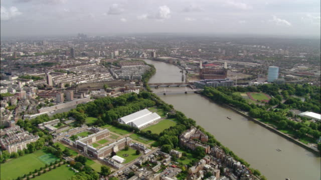 aerial wide shot zoom in approaching london from chelsea with view of albert and victoria bridges and battersea / london, england - flussufer stock-videos und b-roll-filmmaterial