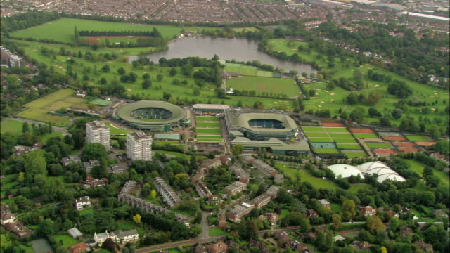 Aerial wide shot zoom in pan residential district with All England Lawn and Tennis Club in background / overhead view tennis club / Wimbledon