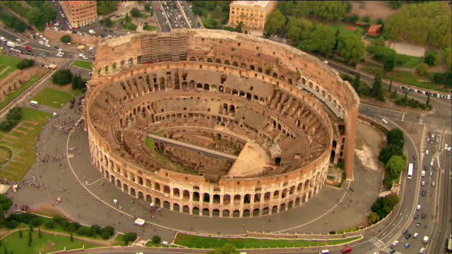 vídeos y material grabado en eventos de stock de aerial wide shot zoom in to interior of the colosseum / rome, italy - anfiteatro