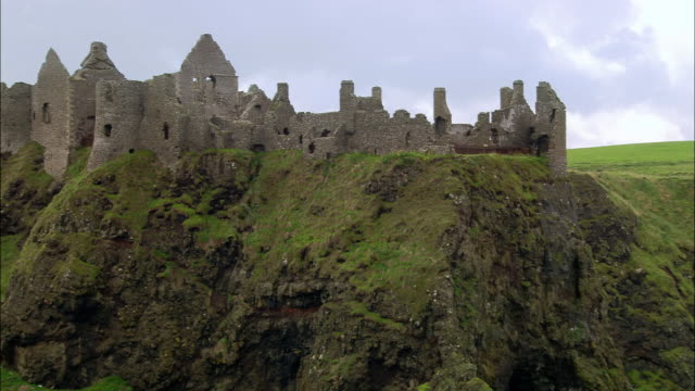 stockvideo's en b-roll-footage met aerial wide shot zoom out dunluce castle and coast / coleraine, ireland - stadsdeel