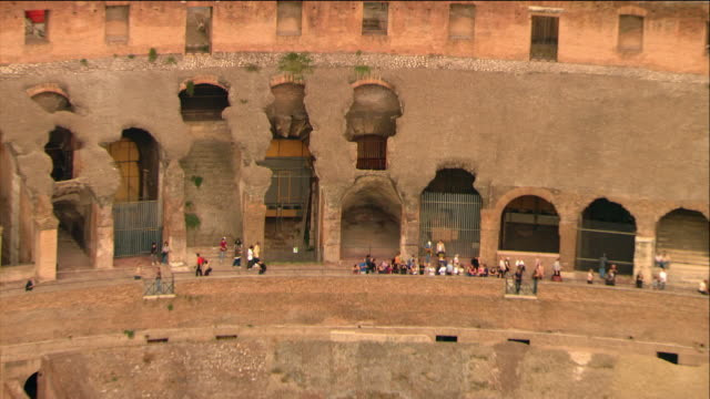 stockvideo's en b-roll-footage met aerial wide shot zoom out tourists milling around the colosseum / rome, italy - colosseum