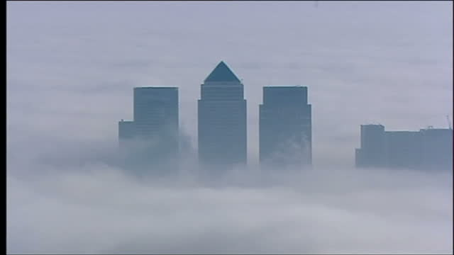 aerial wide shots of the london skyline covered in a thick blanket of fog, with the top of canary wharf skyscrapers visible through the fog on... - london docklands stock videos & royalty-free footage
