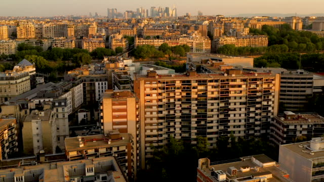 aerial wide view descending low over rooftops in paris france, morning sunrise - île de france stock-videos und b-roll-filmmaterial