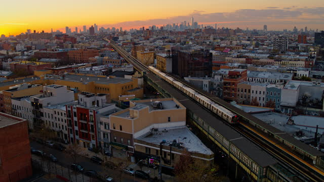 aerial wide-angle high-point view of downtown brooklyn and manhattan skyline from bushwick over the residential area in the sunset, with a train departing from station. drone video with the forward camera motion. - district stock videos & royalty-free footage
