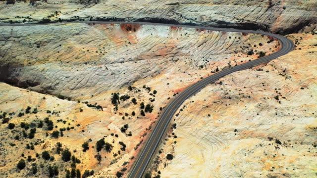 aerial: winding road at grand staircase-escalante national monument, highway in desert - グランドステアケースエスカランテ国定公園点の映像素材/bロール