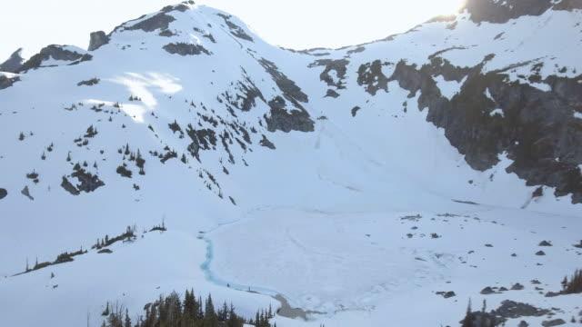 vídeos de stock e filmes b-roll de aerial: winter landscape with frozen lake and rocky mountains in vancouver, canada - distante