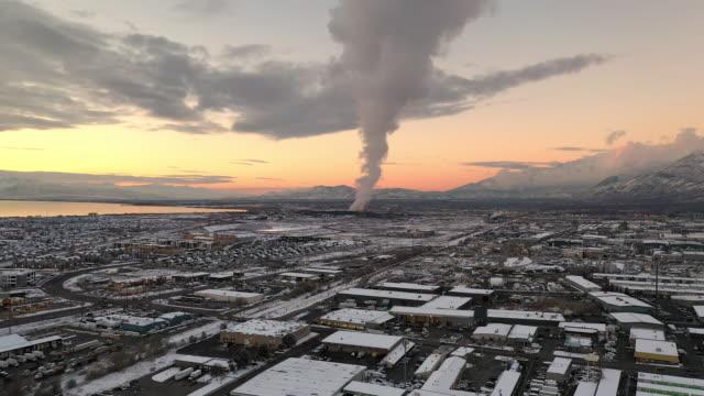 vidéos et rushes de aerial winter sunset view flying towards smoke from factory - aménagement de l'espace
