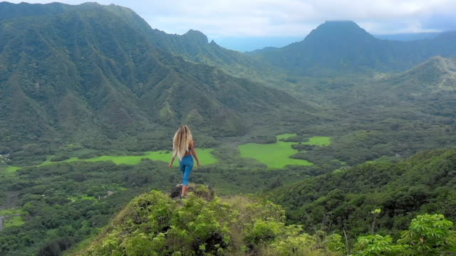 stockvideo's en b-roll-footage met aerial: woman on mountain peak taking in the lush view around her, oahu, hawaii - oahu