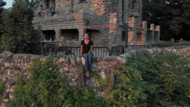 Aerial: Woman Sitting on Stone Wall in Front of Castle