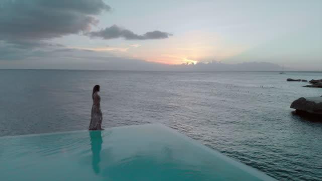 aerial: woman slowly walking on the edge of swimming pool next to the ocean - ドミニカ共和国点の映像素材/bロール