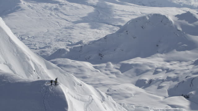 aerial wrap of skiers on summit of large alaskan mountian - helicopter tour stock videos and b-roll footage