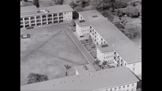 Aerial WS WWII fighter plane flying over military building / Hawaii, United States