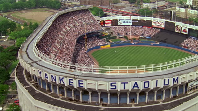aerial yankee stadium and surrounding area / over stadium during game / zoom in spectators in stands / nyc - ニューヨーク・ヤンキース点の映像素材/bロール