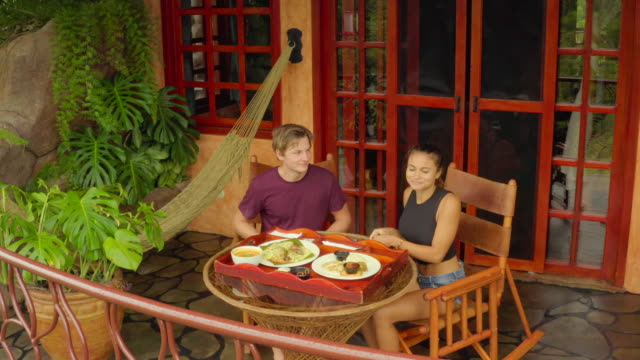 aerial: young couple having lunch on luxurious terrace - patio点の映像素材/bロール