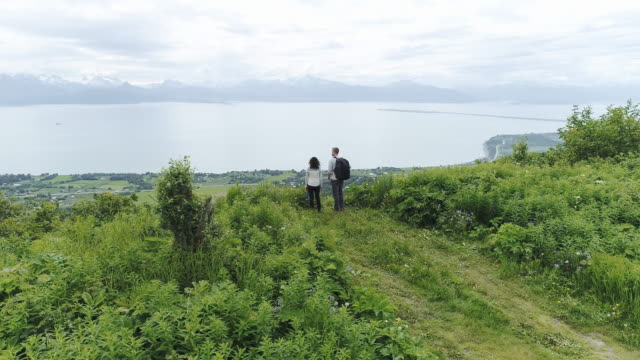 uhd 4k aerial: young interracial couple enjoying a beautiful view of alaska's mountainous coastline after completing a hike - homer alaska stock videos & royalty-free footage