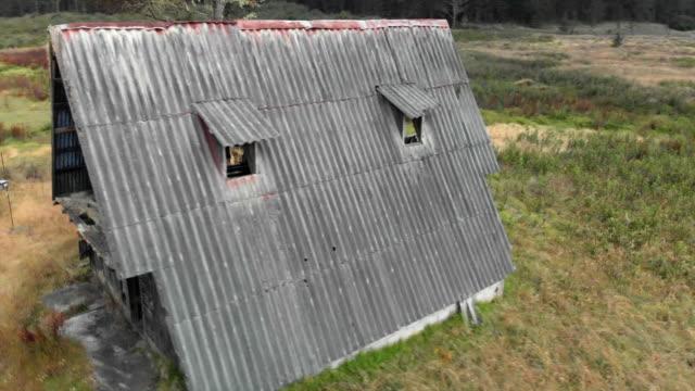 vidéos et rushes de aerial: young men in front of scenic ruinous hut next to other ruins - autre thème
