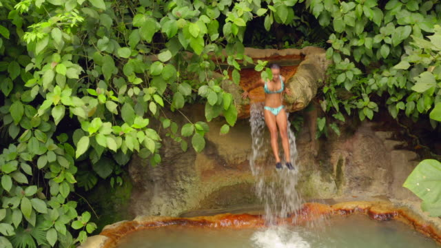 vídeos de stock e filmes b-roll de aerial: young woman jumping from top of hot spring waterfall - costa rica