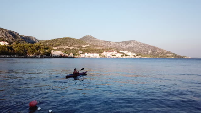 vídeos y material grabado en eventos de stock de aerial, young woman kayaks off hvar island coastline - cultura croata
