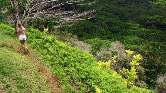 vidéos et rushes de aerial: young woman walking up a trail on a tropical island , moorea, french polynesia - moorea