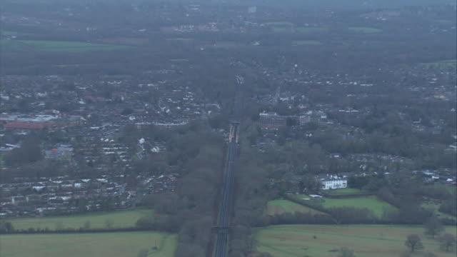 Aerial zoom in across fields to a station in southeast England during train strikes of winter 20162017 UK