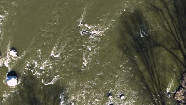 aerial zoom in looking directly down at water flowing over rocks in river - new paltz stock videos and b-roll footage